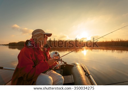 Fisherman in the boat at sunrise moment. - stock photo