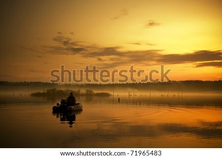Fisherman in the motorboat - stock photo
