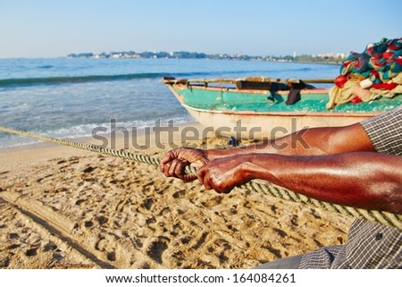 Fisherman is pulling the net out of the sea. - stock photo