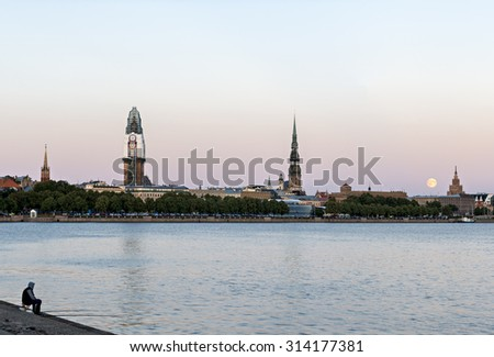Fisherman looking at old city of Riga from left embankment of the Daugava river, Latvia. The image was taken during a rise of supermoon on August 29, 2015.