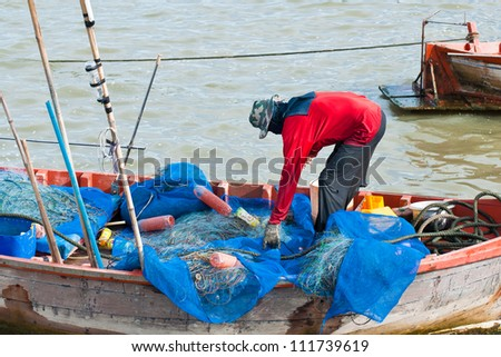 Fisherman mending net in his boat