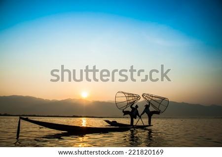 Fisherman of Inle Lake in action when fishing, Myanmar  - stock photo