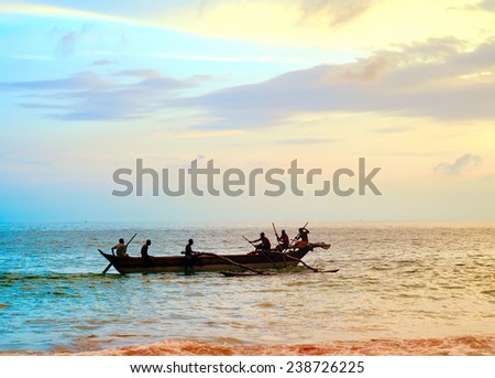 Fisherman on a boat in ocean at sunset, Sri Lanka - stock photo