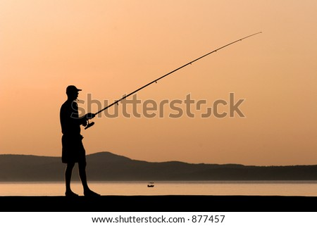 Fisherman on a harbour wall - stock photo