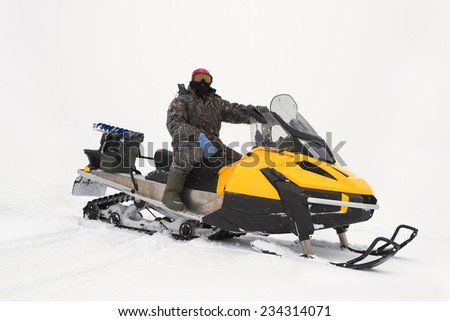 fisherman on a snowmobile rides on winter fishing