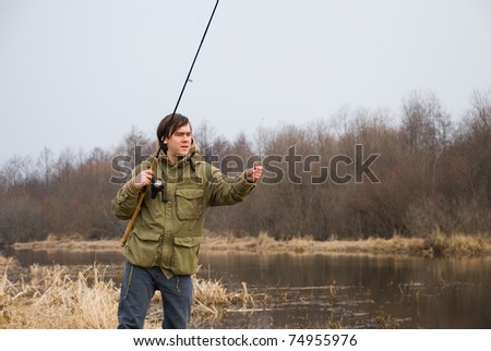 Fisherman on a spring river. - stock photo