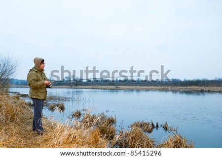 Fisherman on a spring river - stock photo