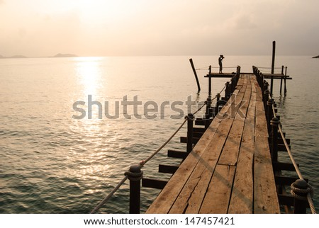 fisherman on boat in the sunrise, Thailand - stock photo