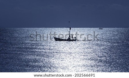 Fisherman on boat silhouette in sea  , Thailand - stock photo