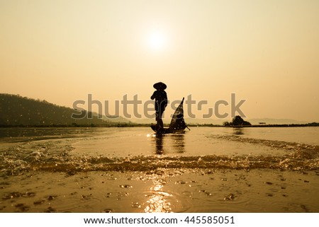 fisherman on boat with sunrise background (focus at fisherman), the Mekong River in Thailand - stock photo