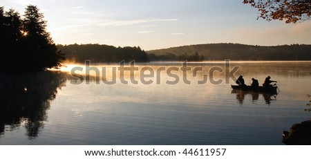 Fisherman on Lake at First Light - stock photo