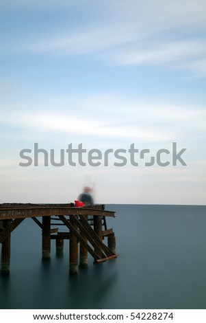 Fisherman on old pier (Long Exposure) - stock photo