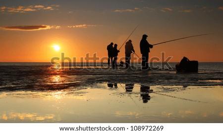 Fisherman on sunrise on the pier - stock photo