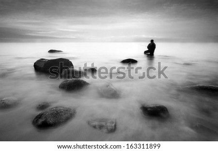 Fisherman on sunrise on the pier  - stock photo