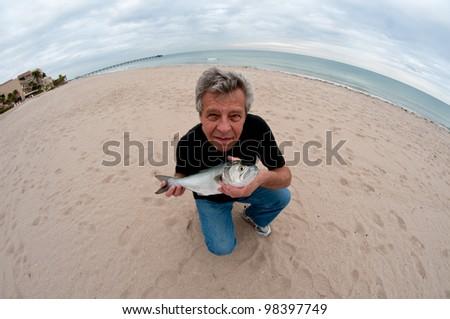 Fisherman on the beach through fish-eye lens - stock photo