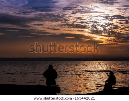 Fisherman on the calm Sunset seaside - stock photo