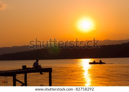 Fisherman on the dock at the sunset.