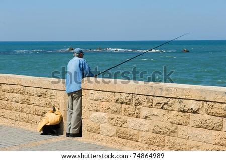 Fisherman on the Mediterranean Coast at Tel Aviv, Israel - stock photo