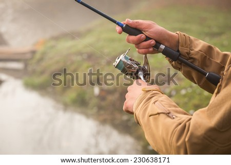 Fisherman on the river bank. Autumn fishing. Fisherman in his hand holding spinning. Fishing, spinning reel, fish, Breg rivers. - The concept of a rural getaway. Article about fishing. - stock photo