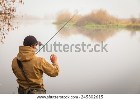 Fisherman on the river bank in sunglasses.Fisherman in his hand holding spinning. Fishing, spinning reel, fish, Breg rivers. - The concept of a rural getaway. Article about fishing. - stock photo