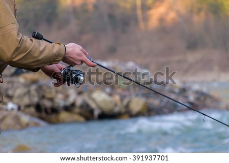 Fisherman on the shore of a mountain river - stock photo