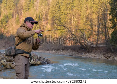 Fisherman on the shore of a mountain river