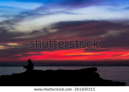 Fisherman on the sunset background, silhouette - stock photo