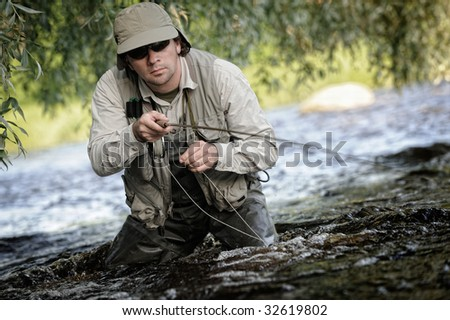 Fisherman on wild river - stock photo