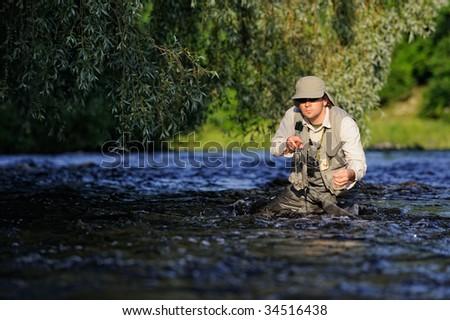 Fisherman on wild river - stock photo