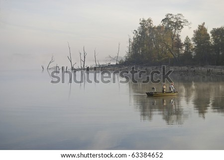 Fisherman out on the Manasquan Resevoir early on this foggy Autumn morning. - stock photo