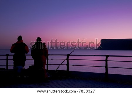 fisherman patiently await a bite as the sun dawns over the coast - stock photo