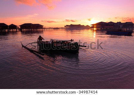Fisherman prepares his traditional boat during sunset at the coastal of beauty tropical island - stock photo
