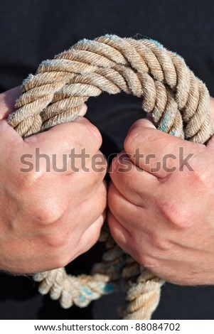 Fisherman's hand is holding a rope. - stock photo
