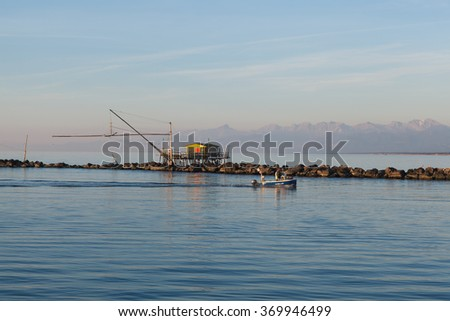 Fisherman's hut and a boat returning along the Arno river to the Marina di Pisa. In the background is a spectacular background with mountains in the late afternoon light. - stock photo