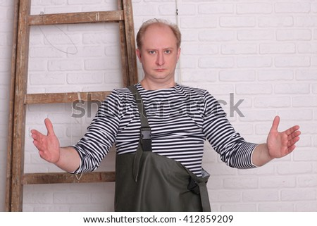 Fisherman shows hands the size of fish on white wall background. - stock photo