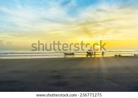 fisherman silhouette at beach with great ray of light - stock photo