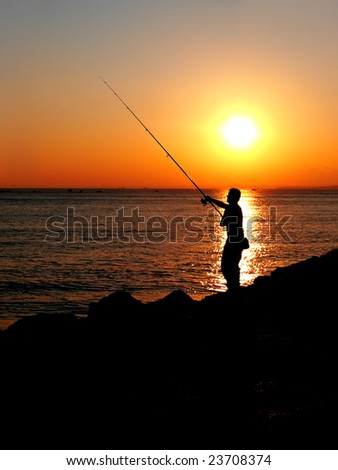 Fisherman silhouette on sunset
