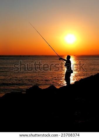 Fisherman silhouette on sunset - stock photo