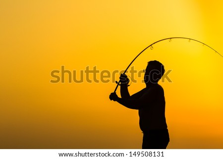 Fisherman silhouette on the beach at colorful sunset - stock photo