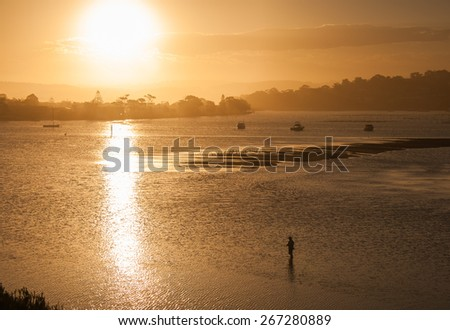 Fisherman silhouette standing in the sea inlet in Merimbula, Australian whale watching town, during sunset - stock photo