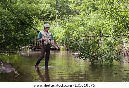 fisherman snagged on a branch in a small trout stream - stock photo