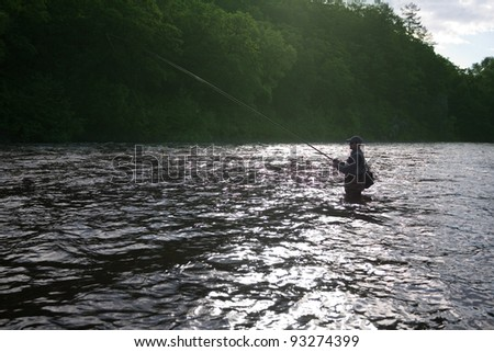 Fisherman standing in the river and catching salmon. Morning. - stock photo