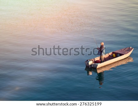 Fisherman standing on a boat and fishing in sea - stock photo