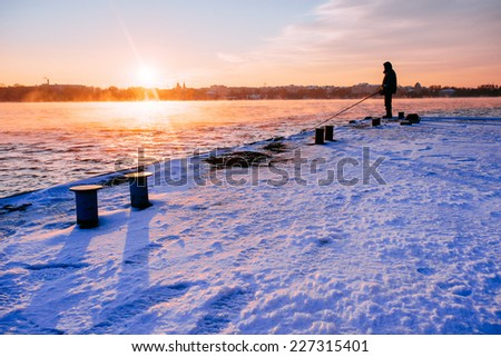 Fisherman standing on a pier at dawn sky background with sun rays and reflected in the sea water  - stock photo