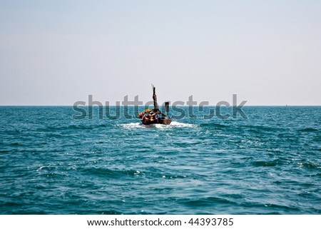 fisherman steers his small wooden boat out to the open sea to go for as catch
