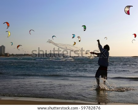 Fisherman throwing a seine in the sea and surfers - stock photo