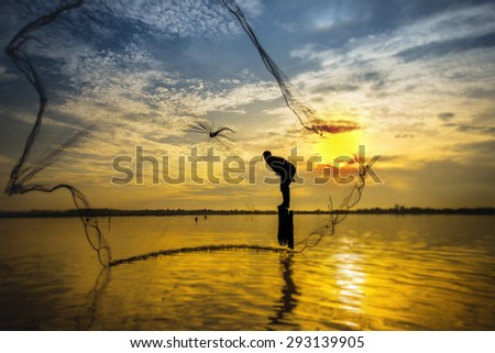 Fisherman throwing fishing net during sunset - stock photo