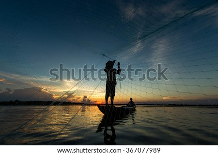 Fisherman throwing net at sunrise, Thailand