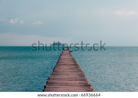 Fisherman throws net from Ocean Pier on tropical island - stock photo