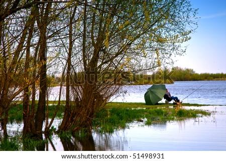 Fisherman under big green umbrella - stock photo